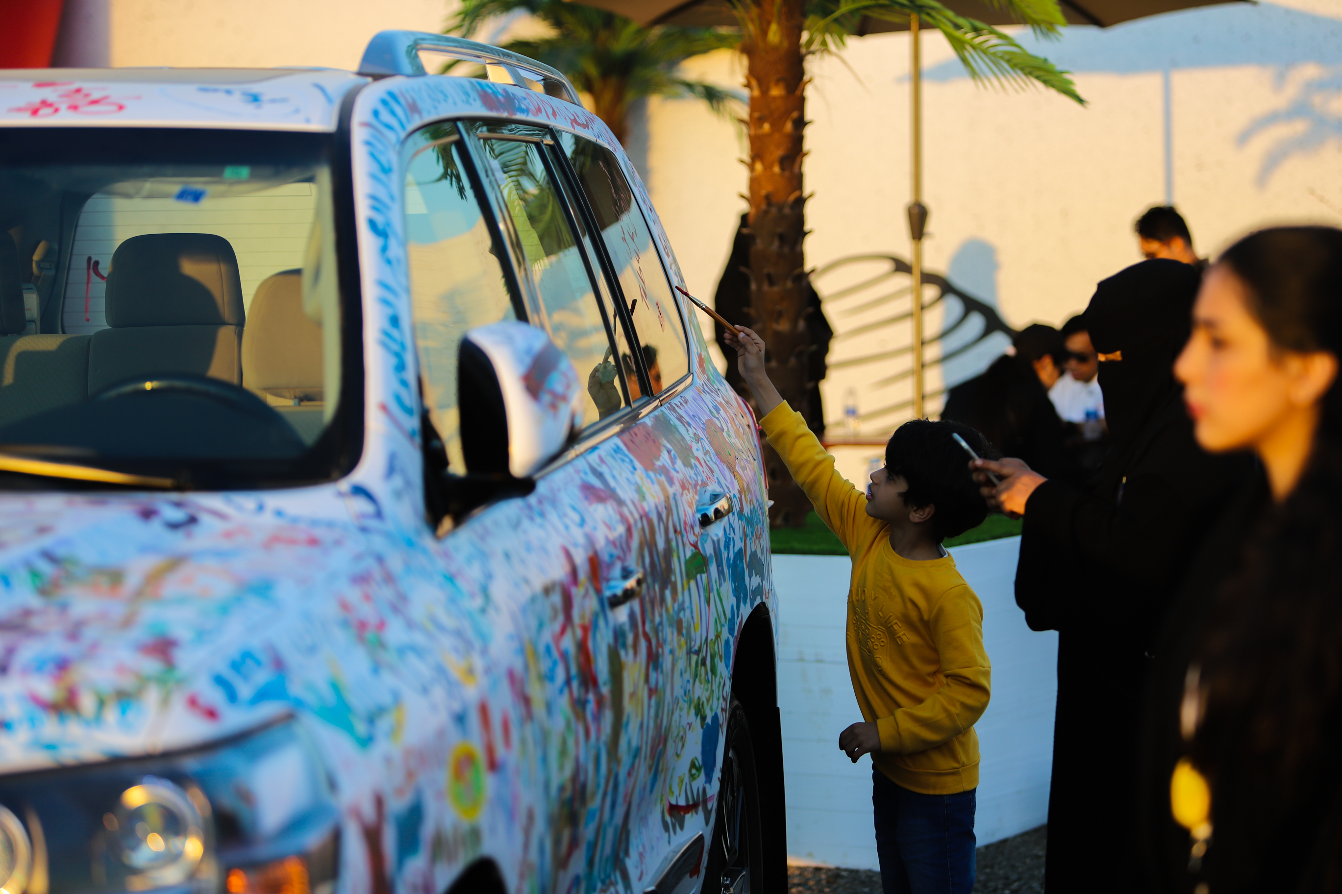 Event attendees were invited to memorialize their participation by writing their names and messages on a Land Cruiser car, in bright and colorful paint.